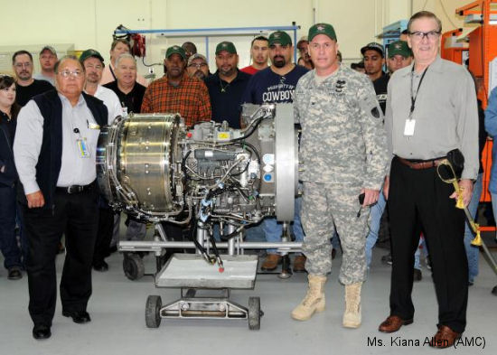 Joe Herrera, Director, Power Train Production; Col. Christopher Carlile, CCAD Commander and Mike Boies, Honeywell Site Manager flank the 400th T55-GA-714 Honeywell engine overhauled at the depot, ready to return to the fight. Surrounding the trio are many of the CCAD artisans involved in producing the engines.