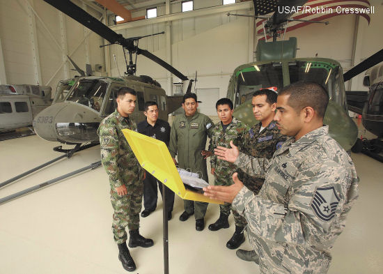 Master Sgt. Guadalupe Arredondo, instructor-supervisor, 318th Training Squadron, right, discusses helicopter towing procedures with, from left to right, students E-1 Powell Murillo, Colombia, O-2 Julio Hortiales, Mexico, E-6 Fernando Toscano, Argentina, E-1 Yamid Camacho, Colombia, and guest instructor PNGI E-8 Mario Ordoñez, Honduras, prior to moving an Army Huey UH-1H helicopter outside the Inter-American Air Forces Academy's Airfield Training Complex High Bay Oct. 1. The UH-1H will be used to train students from Latin American partner nations.