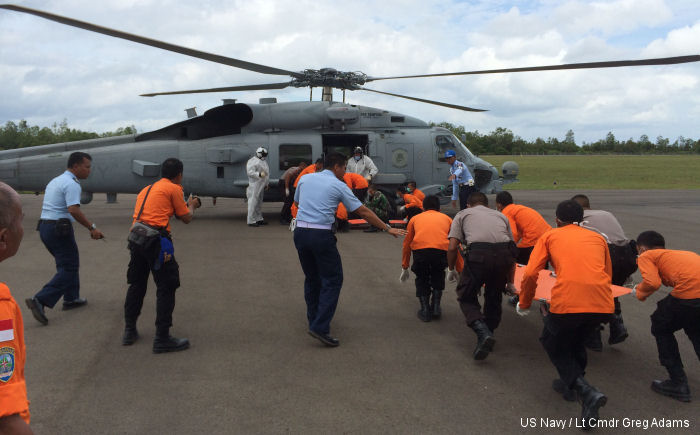 Indonesian authorities at Iskander Air Base approach an MH-60R Seahawk from HSM- 35 to retrieve victims recovered by USS Sampson (DDG-102).