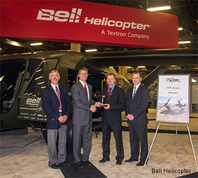 Bell Helicopter President and CEO John Garrison (Center Left) presents Kellsey Justus (Center Right), Astronics Vice President Airborne Power, with a Bell V-280 model at the 2014 Army Aviation Mission Solutions Summit in Nashville, TN. Also pictured from Astronics Michael Ballas (Far Left) and Jon Vandewege (Far Right).