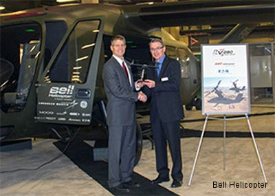 John Garrison, Bell Helicopter President and CEO, presents Mark Schmidt, Sales Director - Eaton Fuel & Motion Control Division, a Bell V-280 model at the 2014 Army Aviation Mission Solutions Summit in Nashville, TN.